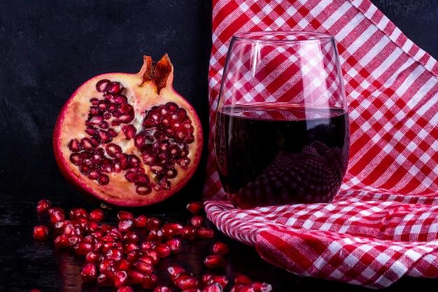 Вид спереди нарезанного граната с гранатовым соком в стакане на красном полотенце Бесплатные Фотографии