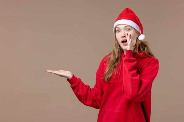 正面図のクリスマスの女の子が茶色の背景に新しい年のクリスマス休暇を呼び出す