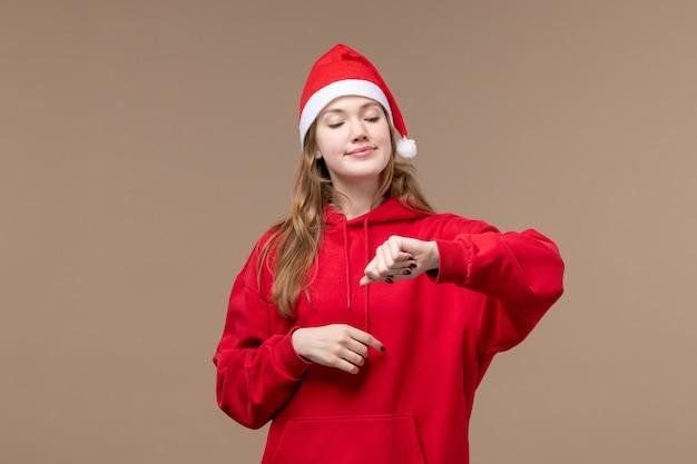 正面図クリスマスの女の子が茶色の背景の休日のクリスマスの感情で時間をチェック