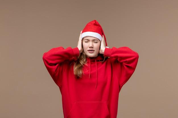 茶色の背景の休日のクリスマスの感情に耳を覆う正面のクリスマスの女の子