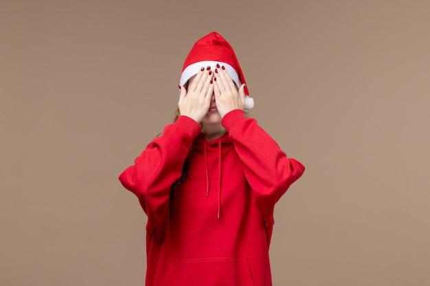 茶色の背景モデルの休日のクリスマスに彼女の顔を覆う正面のクリスマスの女の子
