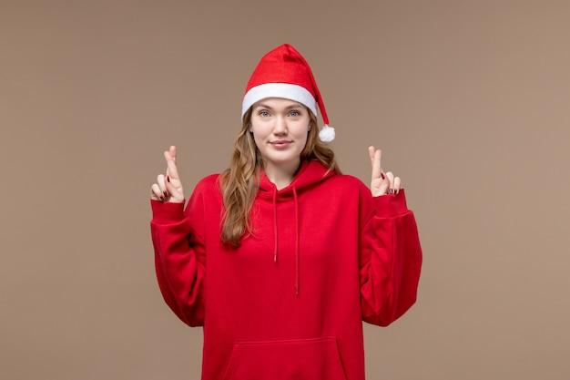 正面図のクリスマスの女の子が茶色の背景の休日モデルのクリスマスに指を交差させます