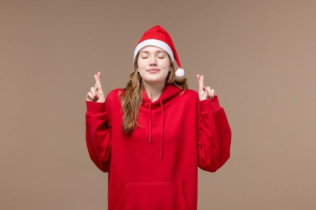 正面図のクリスマスの女の子が茶色の背景モデルの休日のクリスマスに指を交差させます