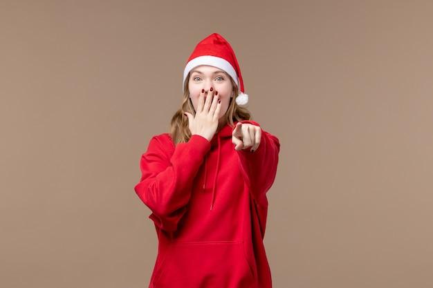 Ragazza di natale di vista frontale che ride sul natale del nuovo anno di feste del fondo marrone