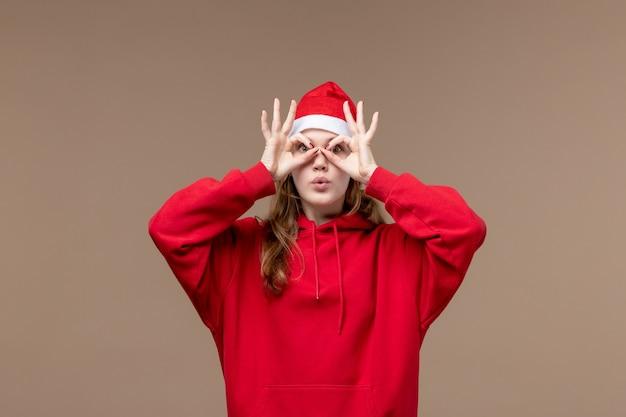 Ragazza di natale di vista frontale che osserva attraverso i suoi occhi sull'emozione di natale di festa del fondo marrone