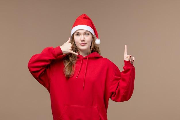 正面図のクリスマスの女の子が茶色の背景の女性の休日のクリスマスにポーズをとる