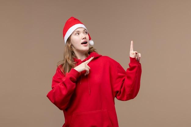 Вид спереди рождественская девушка позирует на коричневом фоне женщина праздник рождество