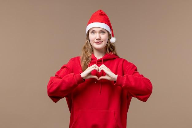 Вид спереди рождественская девушка, отправляющая любовь на коричневом фоне, праздники, новый год, рождество