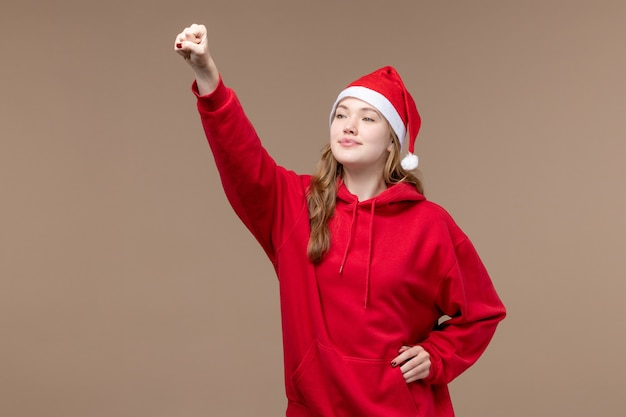 Вид спереди рождественская девушка улыбается и приветствует на коричневом фоне женщина праздник рождество