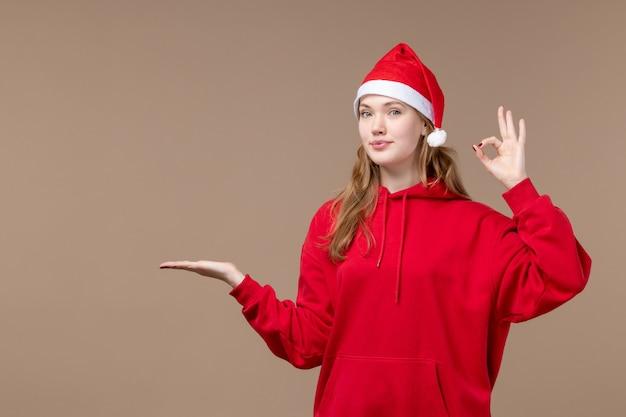 Вид спереди рождественская девушка улыбается на коричневом фоне праздник новый год рождество
