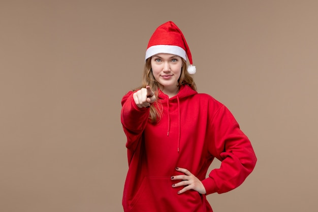 Front view christmas girl smiling and pointing on brown background woman holiday christmas