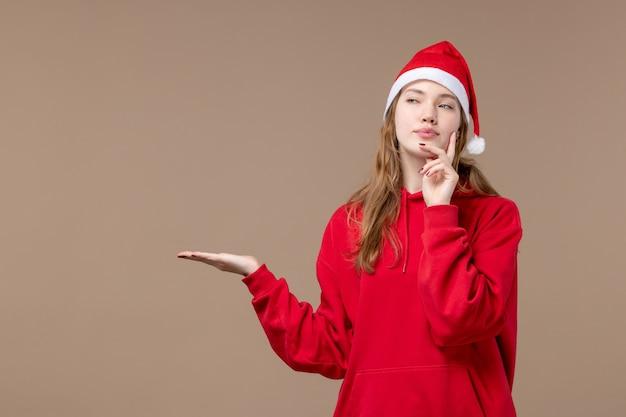 Вид спереди рождество девушка думает на коричневом фоне праздник новый год рождество
