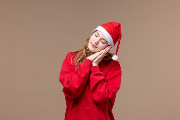 Вид спереди рождественская девушка пытается заснуть на коричневом фоне праздник рождественские эмоции