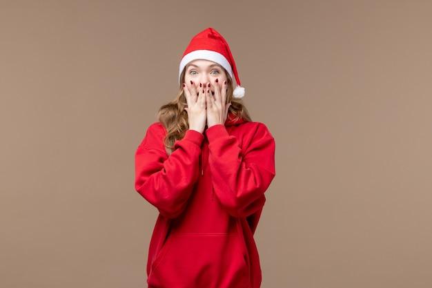 Вид спереди новогодняя девушка с возбужденным лицом на коричневом фоне праздник новый год рождество
