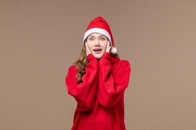 茶色の背景モデルの休日のクリスマスに興奮した顔で正面のクリスマスの女の子