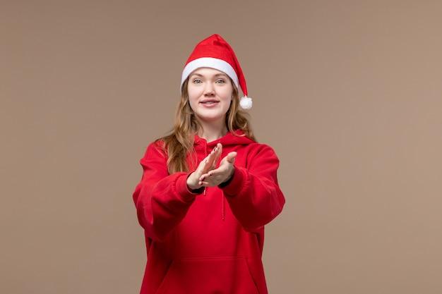 茶色の背景の女性の休日のクリスマスに興奮した顔で正面のクリスマスの女の子