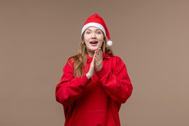 茶色の机の上の興奮した顔を持つ正面のクリスマスの女の子女性の休日のクリスマス