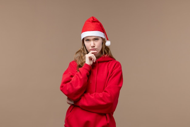 Front view christmas girl with mad face on brown background holiday new year christmas