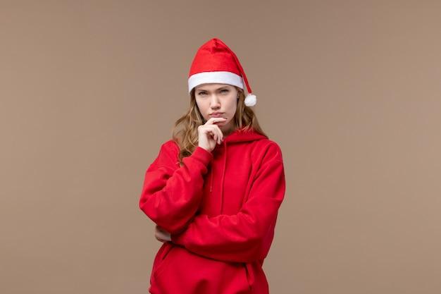 Вид спереди рождественская девушка с безумным лицом на коричневом фоне праздник новый год рождество