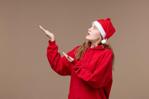 茶色の空間に神経質な顔を持つ正面のクリスマスの女の子