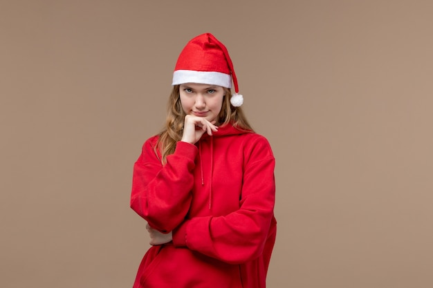 Front view christmas girl with red cape on brown space