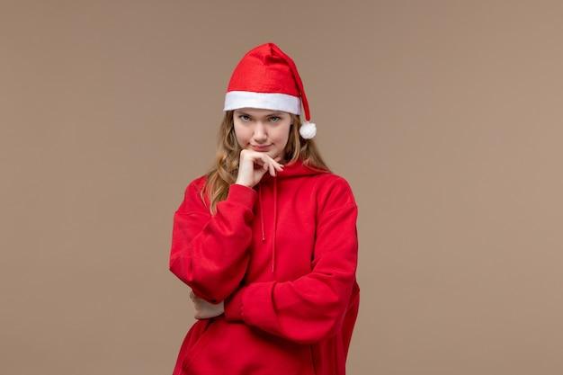 Вид спереди рождественская девушка с красной накидкой на коричневом пространстве