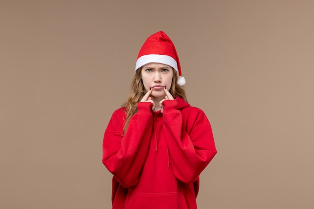 Front view christmas girl with sad face on brown space