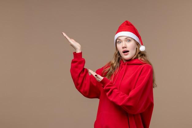 茶色の空間にショックを受けた顔を持つ正面のクリスマスの女の子