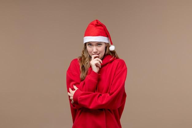Вид спереди рождественская девушка с застенчивым выражением лица на коричневом фоне модель праздник рождество