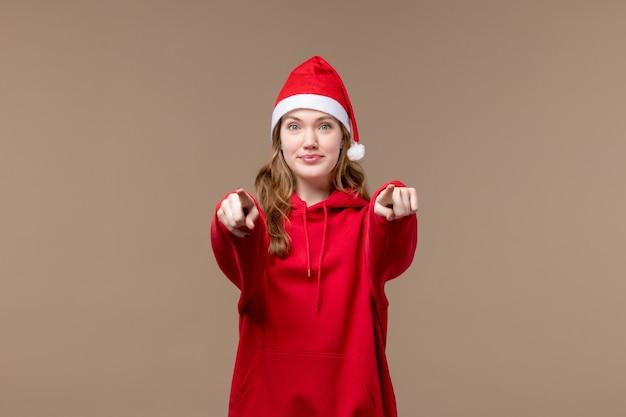 Вид спереди рождественская девушка с улыбающимся лицом на коричневом фоне праздники новый год рождество
