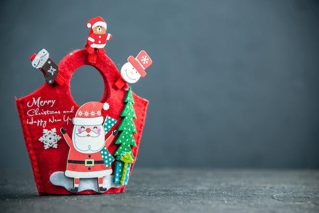 Vista frontale dell'umore natalizio con accessori decorativi e confezione regalo di capodanno su superficie scura