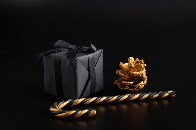 Vista frontale del regalo di natale con bastoncino di zucchero e pigna