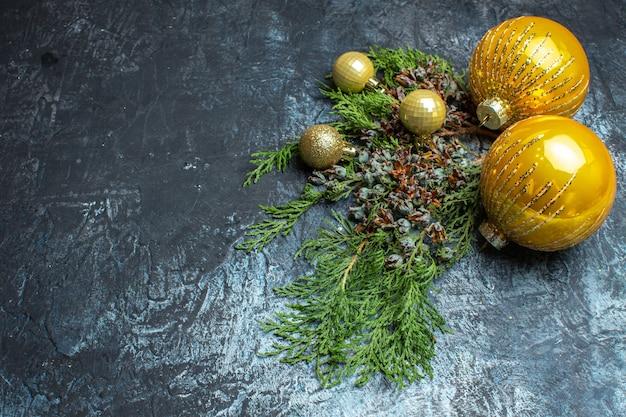 明るい暗い背景に緑の枝を持つ正面のクリスマス ツリーのおもちゃ