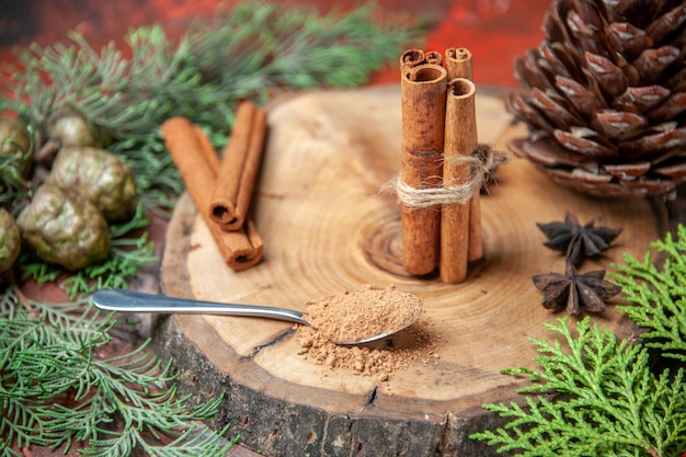 Front view cinnamon sticks cinnamon powders pinecone anises on wood board spoon with cinnamon powder on dark