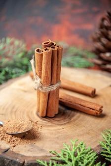 Vista frontale bastoncini di cannella polvere di cannella pigna su tavola di legno su oscurità