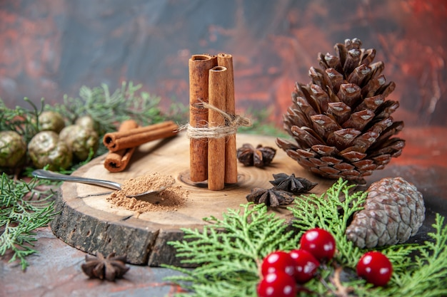 Front view cinnamon sticks on wood board cinnamon powders pinecones anises on dark