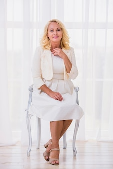 Front view classy woman sitting on chair
