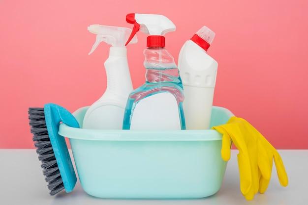 Vista frontale delle soluzioni detergenti nel secchio con guanto e pennello