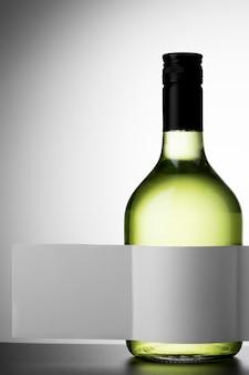 Vista frontale della bottiglia di vino trasparente con etichetta vuota e copia spazio
