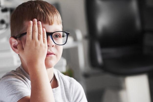 正面図。手で右目を閉じます。新しい黒い眼鏡で視力をチェックしている少年。