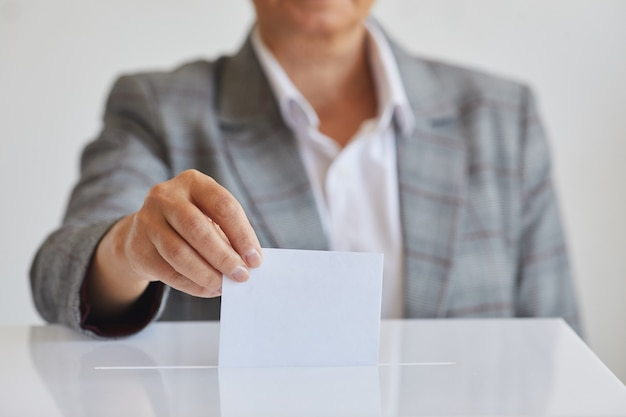 Front view close up of female hand putting vote bulletin in ballot box against white surface on election day, copy space