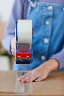 Вид спереди крупным планом неузнаваемой молодой женщины, упаковывающей коробки с помощью диспенсера для ленты во время переезда или переезда