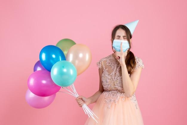 Ragazza di occhi chiusi vista frontale con cappuccio del partito e mascherina medica che fa segno di shh che tiene palloncini colorati