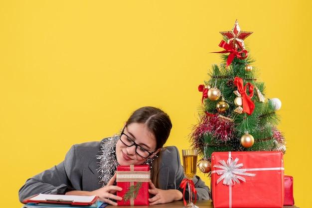 Вид спереди закрытые глаза молодая девушка в очках сидит за столом, держа в руках подарочную рождественскую елку и подарочный коктейль