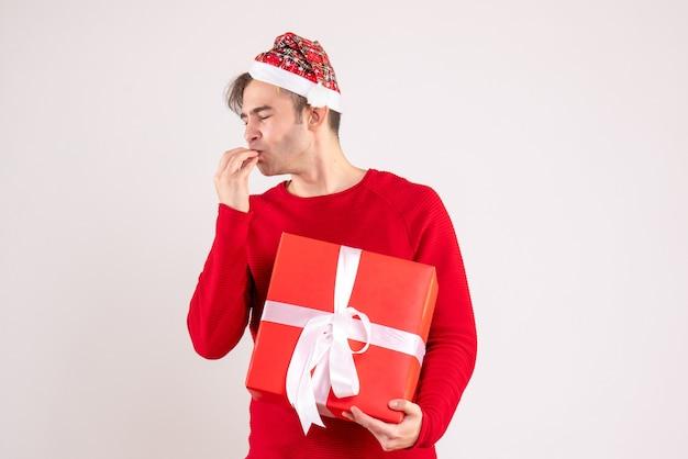 전면보기 흰색 배경에 서있는 산타 모자와 눈 젊은 남자를 폐쇄