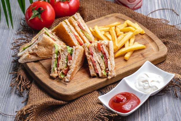 Вид спереди клубный бутерброд с картофелем фри, кетчупом с майонезом и помидорами