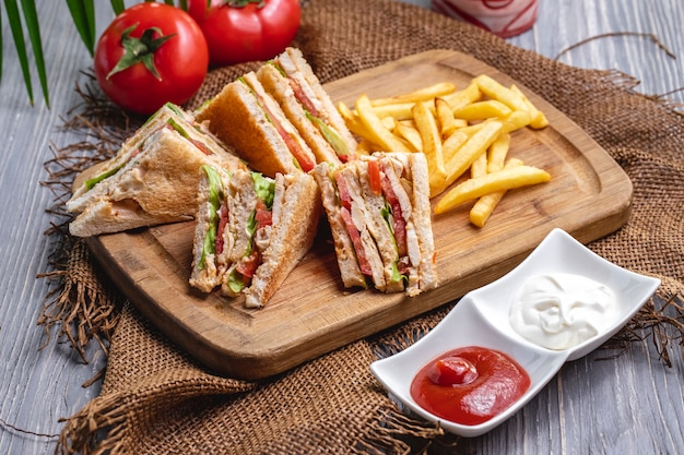 Front view club sandwich with french fries ketchup with mayonnaise and tomatoes