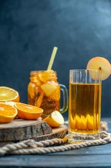 暗い孤立した背景の上の木の板に正面のカクテルカットオレンジとリンゴ 無料写真