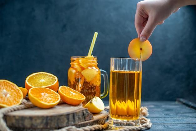 暗い孤立した背景の上の木の板に正面のカクテルカットオレンジとリンゴ