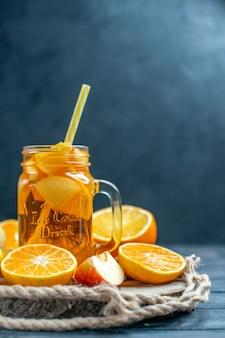 Апельсины и яблоки нарезанные спереди коктейль на деревянной доске на темном изолированном фоне
